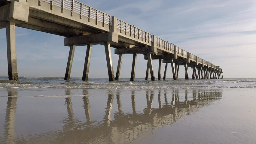 Gulf of mexico surf pounds against pilings of a fishing for Jacksonville fishing pier