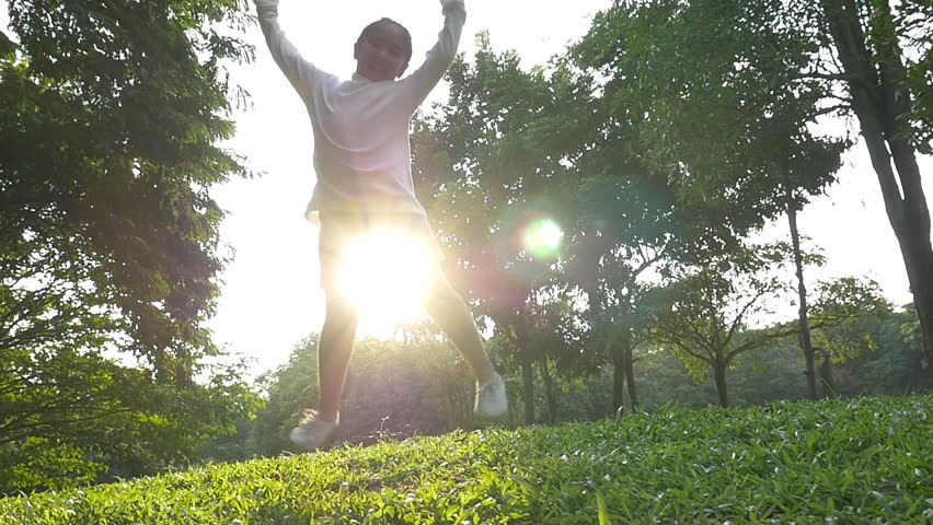 Slow motion shot : Happy Asian little girl jumping in the park with sunlight