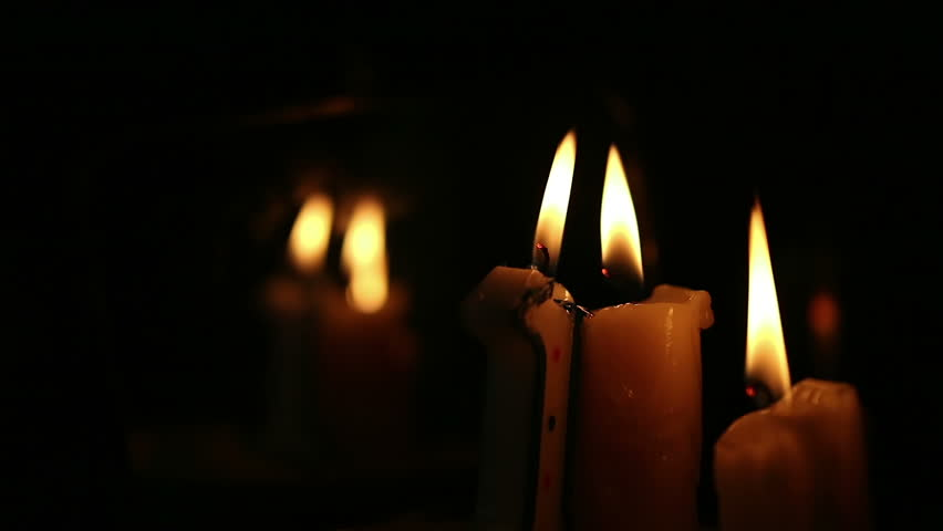 Paraffin candles are lit in the darkness in front of a mirror. Mystic theme. The focus changes from the front of the background. Very small depth of field.
