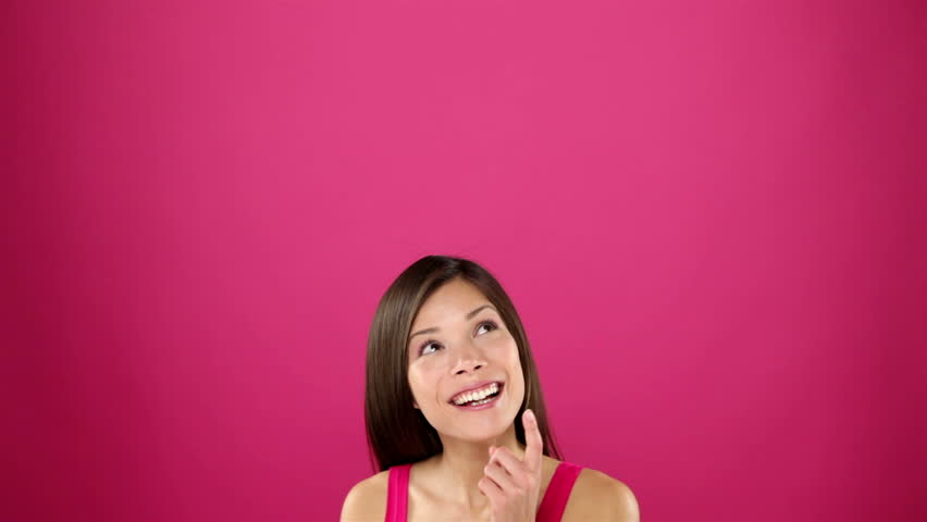 Happy thinking woman looking around at copy space smiling happy and cheerful. Joyful young beautiful multiracial Asian / Caucasian female model on pink background. - HD stock video clip
