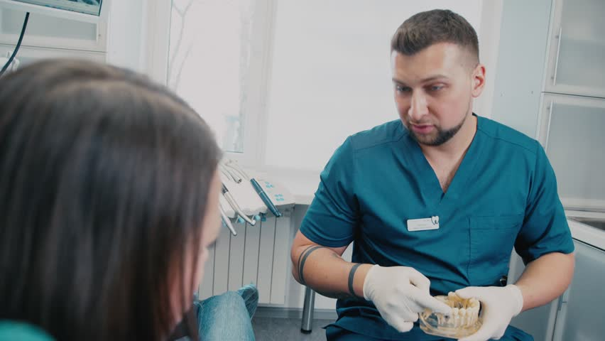 The dentist tells the patient about wisdom teeth. Male dentist. Dental surgeon. The doctor's consultation. At the dentist's office. Dentist looking at the patient and holding a dental model. | Shutterstock HD Video #21150085