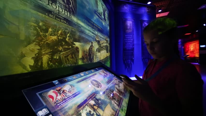 MOSCOW - AUG, 30, 2016: Girl (with model release) touch interactive screen with text in history park Russia - My History in VDNKh. Basis of exposition in Park is history of Rurik and Romanov. | Shutterstock HD Video #21165880