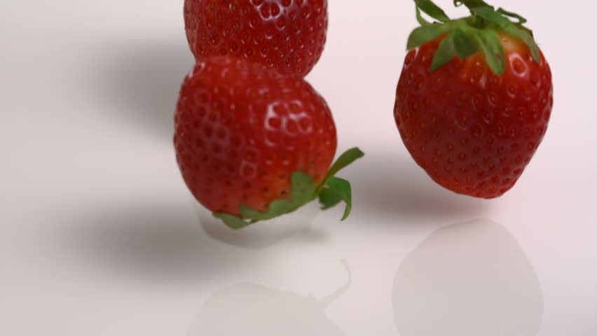 Slow-motion strawberry into milk - HD stock video clip