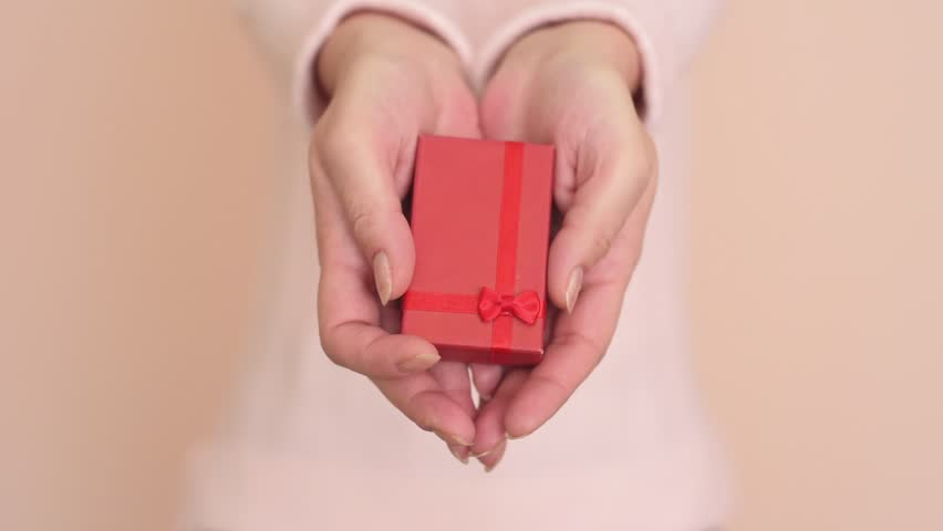 Hands of a woman showing a gift: little red box with a ribbon | Shutterstock HD Video #21287164