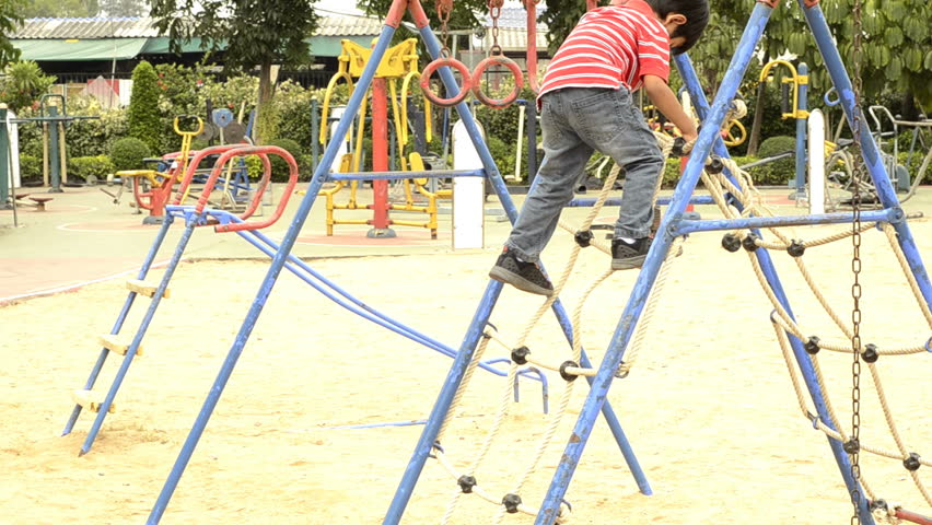 Young boy climbing down a rope ladder in a playground. - HD stock video clip
