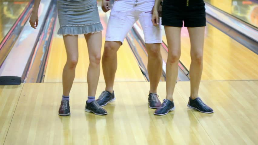Two girls with one guy dance in bowling club, only legs are visible - HD stock footage clip
