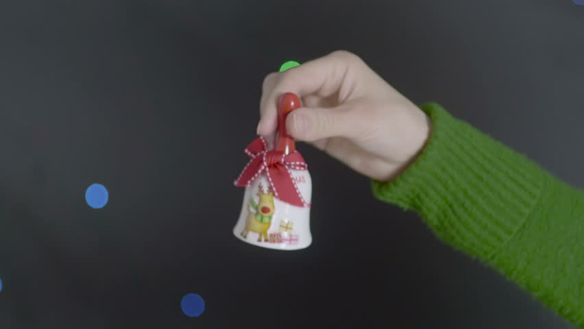 Close-up view of Christmas hand bell with red ribbon in female hand #21373267