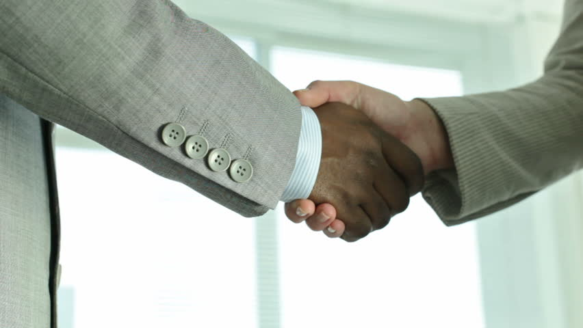 Two positive businesspeople shaking hands indicating a concluded deal
