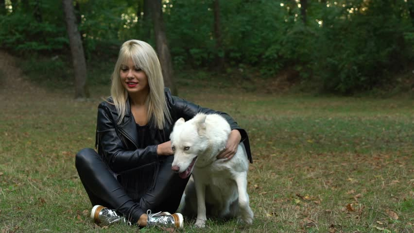 SLOW MOTION: Attractive Caucasian blonde woman in forest surroundings with a white albino husky dog. | Shutterstock HD Video #21560926