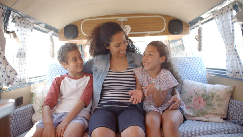 Smiling mum and kids travelling in the back of a camper van | Shutterstock HD Video #21591904
