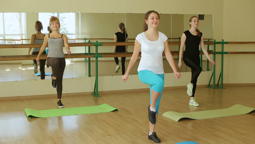 Aerobics class stretching together led by instructor at