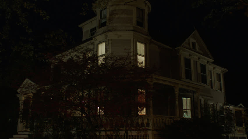 Night then tilts up left beige wood clapboard house , wrap around porch, back porch, bay windows, turret, dormers, autumn, fall trees, lights on, (Oct 2012)