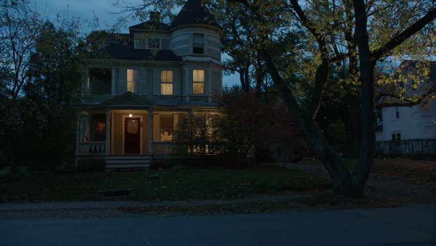 Dusk then pans left along front beige wood clapboard house , wrap around porch, bay windows, turret, dormers, red screened door, autumn, fall trees, lights on, breezy, cloudy (Oct 2012)