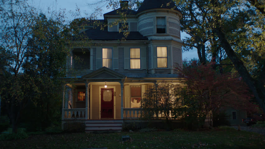 Dusk late day tilt tree front beige wood clapboard house , wrap around porch, bay windows, turret, dormers, red screened door, autumn, fall trees, lights on, breezy, cloudy (Oct 2012)