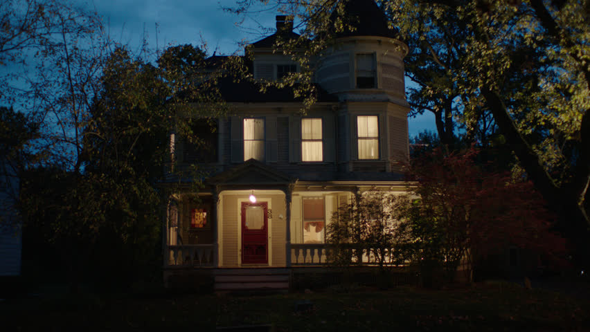 Dusk Magic Hour front beige wood clapboard house , wrap around porch, bay windows, turret, dormers, red screened door, autumn, fall trees, lights on, breezy, cloudy, car (Oct 2012)