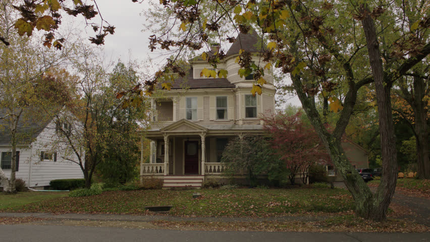 Day pan right neighbor's house beige wood clapboard house , wrap around porch, bay windows, turret, dormers, red screened door, autumn, fall trees, (Oct 2012)