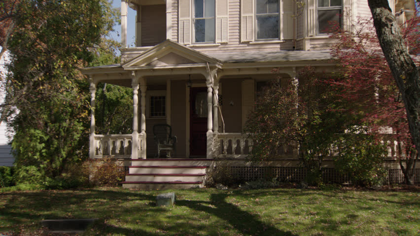 Day then pans left along beige wood clapboard house , wrap around porch, bay windows, screened red door, dormers, autumn, fall trees (Oct 2012)