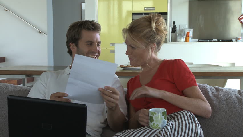 MEDIUM SHOT PAN OF A COUPLE LOOKING AT FINANCES  - HD stock footage clip