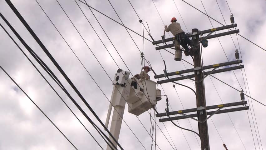 Three workers (two in a cherry picker) repair powerline.