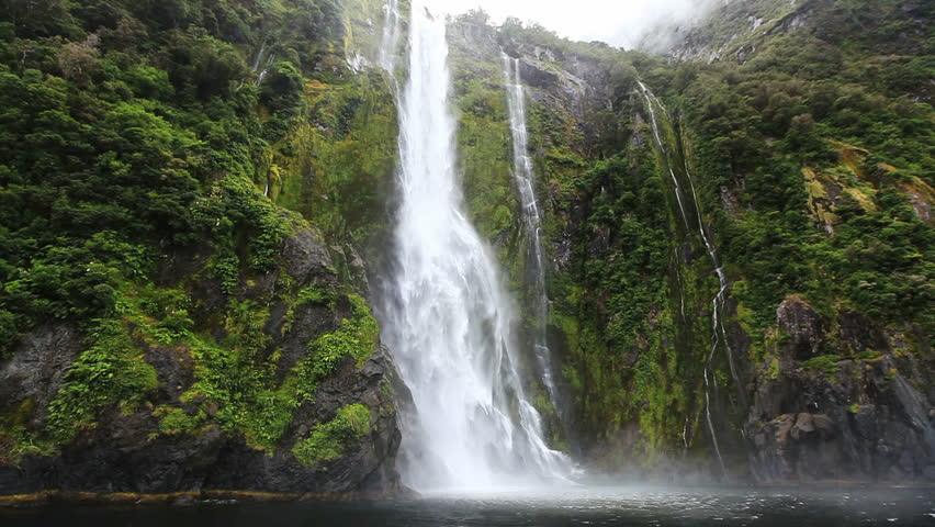 Close approach to waterfall by boat, Milford Sound Fjord. South Island, New Zealand.
