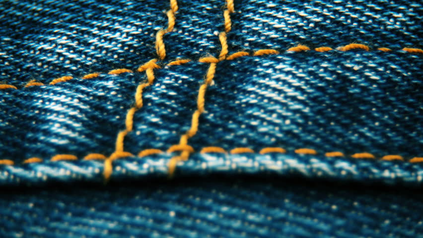 Extreme close-up pan shot of the dark blue pair of jeans' pocket stitched with bright orange thread. Video UHD 3840x2160. | Shutterstock HD Video #22169920