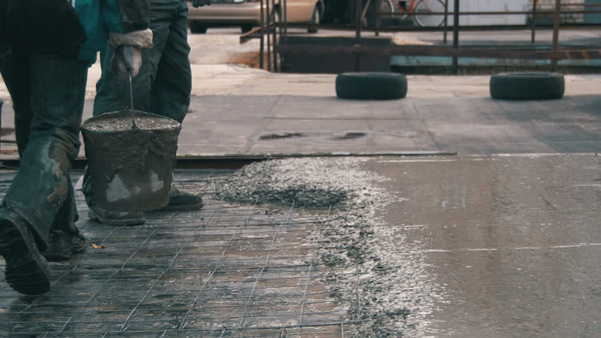 Pouring, laying concrete at the construction site using buckets of cement. Building, concrete work on the roof. Alignment of the concrete screed. Workers pour the solution on the roof. Leveling wet   Shutterstock HD Video #22288090