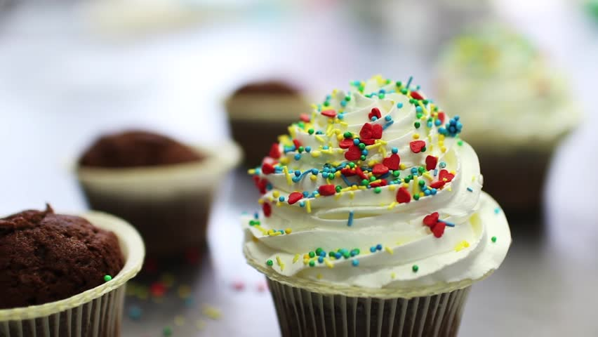 Decorating of chocolate cupcakes with cream, Close up of hand sprinkling topping onto fresh cupcakes #22393894