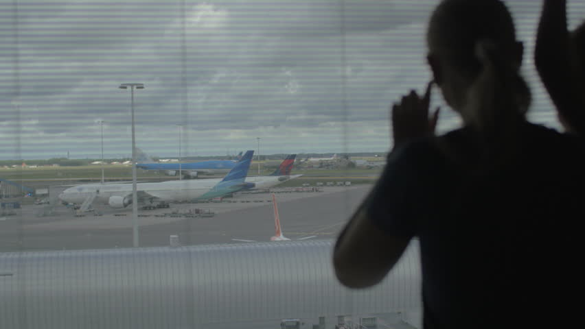 Mother embracing son and they looking at the planes through window in airport. Loving family waiting for flight | Shutterstock HD Video #22434196