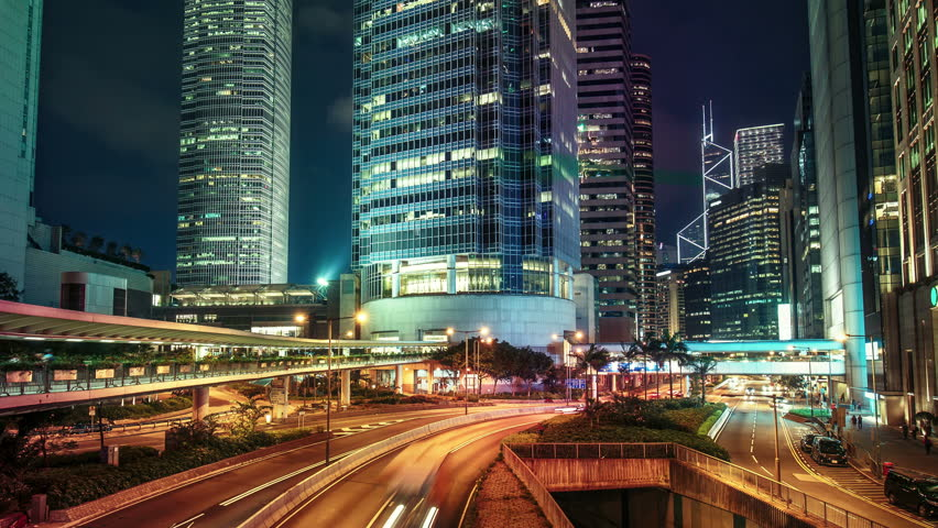 Roads with car trails in Hong Kong financial district at night. Scenic view of big illuminated city with skyscrapers and fast moving traffic. Colourful 4K Time lapse.    Shutterstock HD Video #22446310