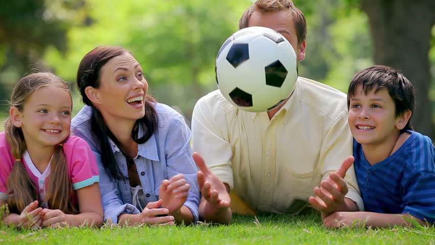 Smiling family trying to catch a soccer ball while lying in a park