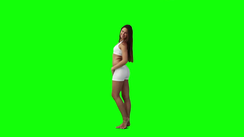 A woman is doing poses for the camera against a green background - HD stock footage clip
