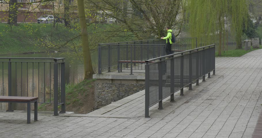 A Tall Man Leans on a Metal Fence, Behind Which a River Begins. the Man is in a Green Zone of a City of Opole (Poland). he Stands on a Bridge and Beholds a Flow of Water.   Shutterstock HD Video #22511758