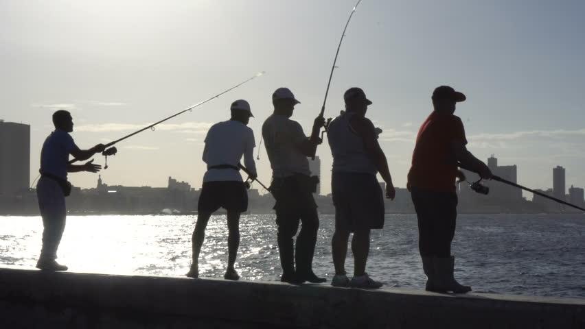 HAVANA, CUBA - NOVEMBER 05, 2016: Young man caught a fish on the pier of Havana at sunset   Shutterstock HD Video #22613836