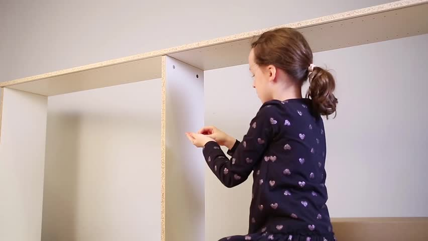 Young girl assembling new furniture | Shutterstock HD Video #22738783