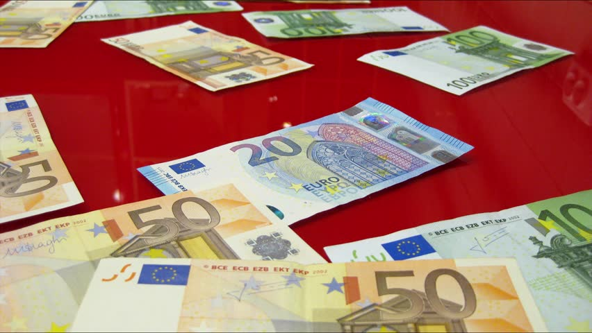 Euro banknotes of different denominations are appearing randomly on a red glass surface. | Shutterstock HD Video #22740160