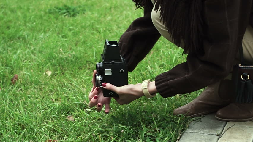 Young woman is taking photos on a old vintage film camera at the autumn park. HD | Shutterstock HD Video #22925560