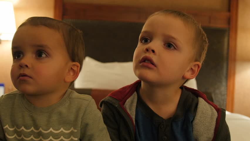 Adorable little boys watching the Television in their hotel room at night with their family #22935784