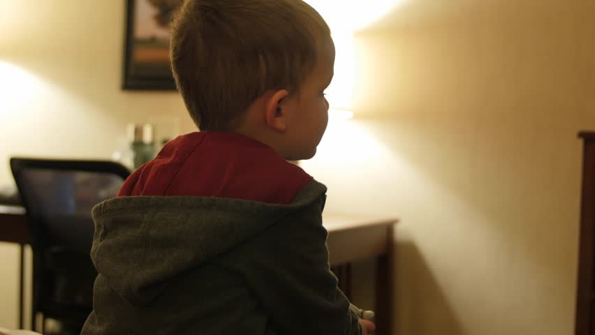Adorable little boys watching the Television in their hotel room at night with their family #22935802