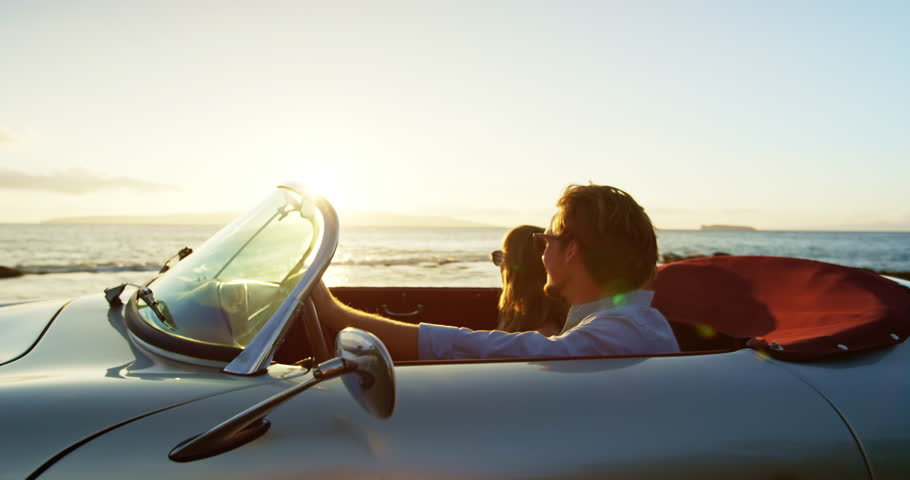 Happy Couple Driving into Sunset in Classic Vintage Sports Car by the Ocean. Romantic Sunset Drive. Shot on RED