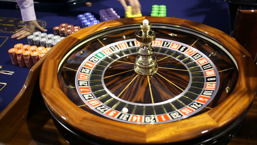 Roulette table in casino. Ball in the rotating gambling machine. Wooden roulette wheel. Casino croupier releases roulette white ball. | Shutterstock HD Video #23122948
