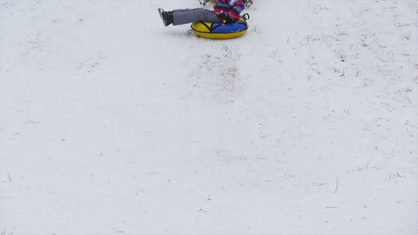 Winter, leisure, sport, and people concept - happy teenage boy or young man sliding down on snow tube over mountain background | Shutterstock HD Video #23156617