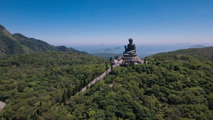 Aerial drone flight towards the peaceful Tian Tan bronze Buddha statue, part of the Po Lin monastery in Hong Kong, located in a beautiful mountain setting.    Shutterstock HD Video #23168065