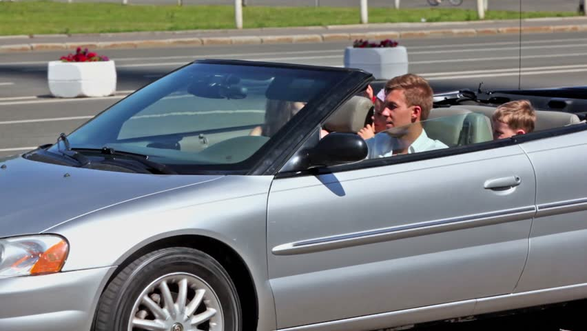 Young couple with two kids pass by in cabriolet with window moves up and down - HD stock video clip
