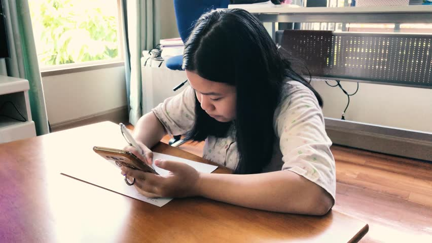 Asian girl,Teenager doing homework, calculating math on smartphone at home ,selective focus ,vintage style | Shutterstock HD Video #23179540