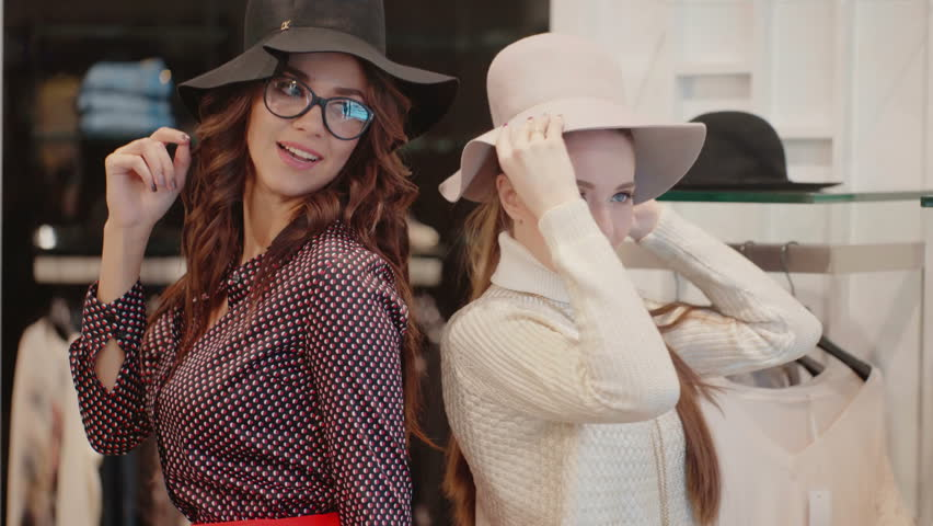 The girl with long hair wearing glasses and a brunette with blue eyes are smiling, posing for the camera wearing hats   Shutterstock HD Video #23180602