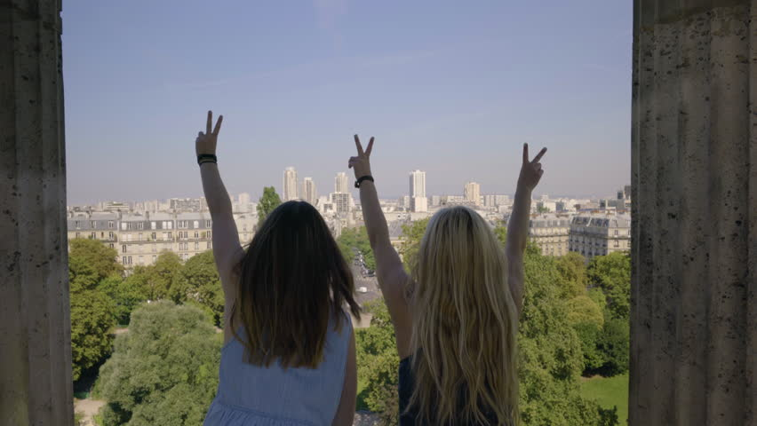 Young Women Raise Their Arms Up And Make Peace Signs From The Historical Temple De La Sibylle In The Parc Des Butte Chaumont In Paris, France | Shutterstock HD Video #23180908