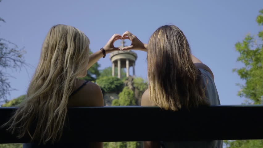 Young Women Create A Heart Shape With Their Hands, Around The Temple De La Sibylle In The Parc Des Butte Chaumont In Paris, France | Shutterstock HD Video #23180917