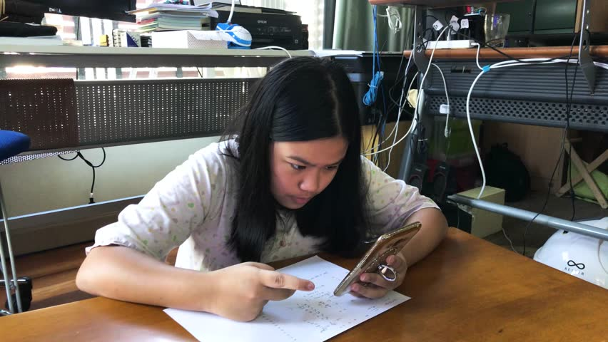 Asian girl,Teenager doing homework, calculating math on smartphone at home ,selective focus ,vintage style | Shutterstock HD Video #23181646