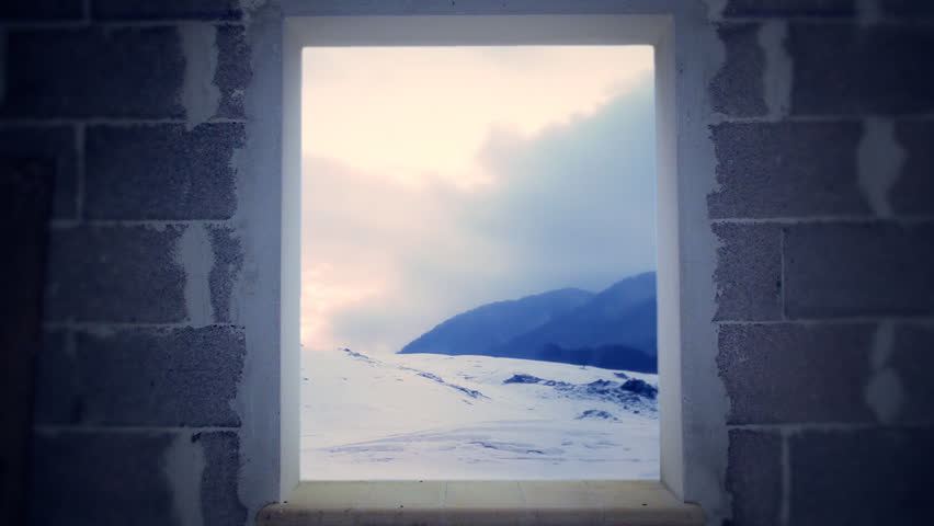 Morning or dusk on a mountain full of snow. Seen from a window in a bare room.