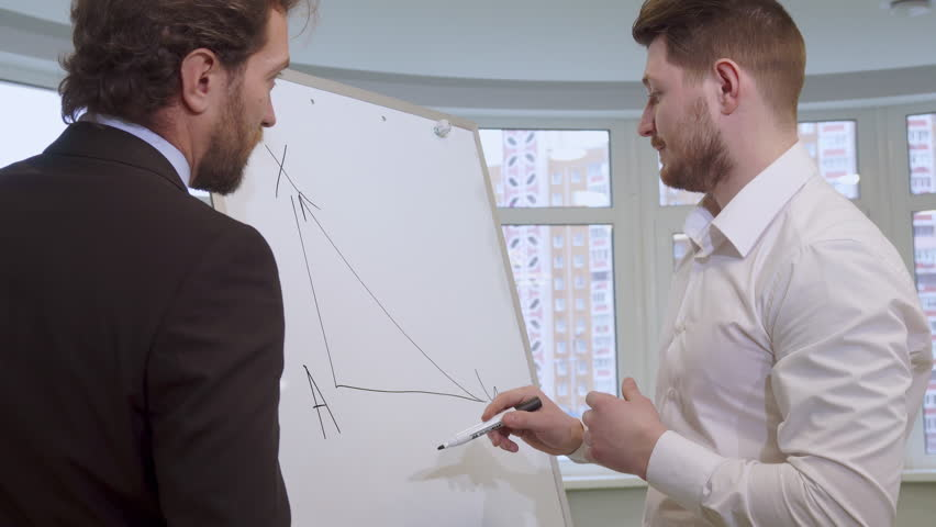 Attractive young businessman drawing on the flip chart. Handsome bearded man in white shirt explaining something to his partner. Middle aged caucasian male manager in suite listening to his colleague | Shutterstock HD Video #23187073